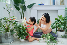 Beautiful Pregnant Young Woman And Little Daughter Watering Plants On Her Balcony