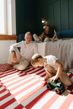 Beautiful Family With Small Children In A Cozy Modern Room.
