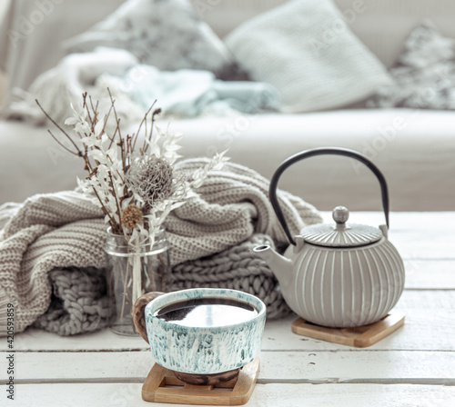 Fotografia Cozy Scandinavian composition with teapot, ceramic cup of tea and decor details