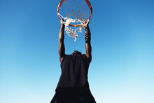 Young Man Hanging From A Basketball Hoop