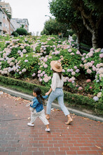 Mom And Daughter Walking In City