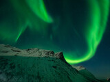 Northern lights over snow covered peaks