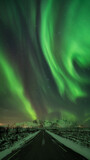 Wonderful northern lights over paved road in arctic norway