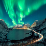 Northern lights over snow covered fjord in Norway