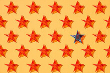 One Blue Star Standing Among Other Red Stars On Orange Color Background