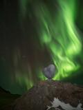 Bright northern lights over stone heart at uttakleiv beach