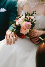 Bride Holding A Pastel Pink Colored Wedding Bouquet And Groom Holding Hand Tender On Knee Of Bride