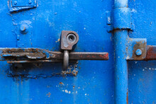Old Rusty Lock On The Bright Blue Door Of A Metal Sea Container, Close-up, Dirty Padlock On The Rusted Handle Of A Closed-door Of Aged Painted And Weathered Container