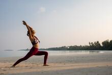 Young Asian Woman On A Maldivian Beach Doing Yoga
