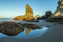 USA, Oregon, Bandon Beach. Rock Formations And Reflection In Beach Water.