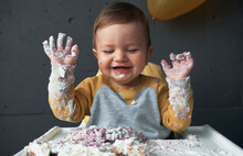 Baby Boy Laughing With Smashed Cake On His Hands