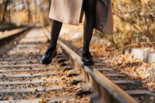 A Girl Walks In The Autumn Park On The Tram Tracks.
