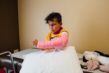 Boy Sitting In Doctor's Office With A Broken Arm.
