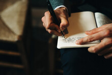 Male Hand Writing Down Words In A Notebook