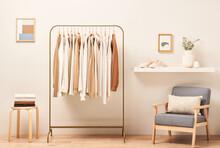 Armchair And Shelf Near Clothes Rail