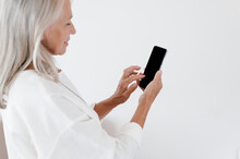 Happy Gray Haired Woman Browsing Smartphone