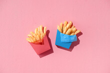 Carton Boxes With Delicious French Fries On Pink Background