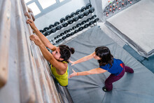 Vigorous Woman With Instructor Climbing Up Wall