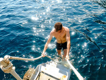 Man Climbing Ladder After Swimming In The Sea