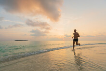 A Caucasian Man Is Running Bare-feet On A Maldivian Beach In The Early Morning Hours