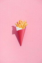 Baked Potatoes Wedges In Red Paper Cone On A Pink Background.