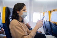 Woman With Mask Flying On A Plane.