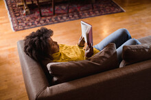 Black Woman Reading A Book Inside Her House. Lifestyle Images.