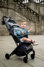 Baby Sitting In Carriage On Pavement