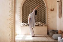 Slim Woman Doing Crescent Moon Pose In Oriental Room