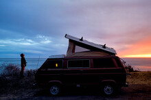 Yong Traveller Standing Next To Her Vintage Campervan Over A Beautiful Sunset In The West Caast Of California