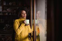 Black Woman Drinking Tea Near A Window.