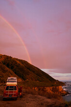 Rainbow Sunset Moment With A Vintage Campervan And The Magnificent Views Of The Pacific West Coast In California During A Roadtrip.