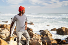 Surfer Exploring Rocky Shoreline For Surf