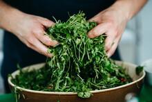 Men Mixing Salad With Hands In Big Bowl