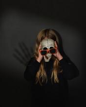 Child Holding Halloween Skeleton Face