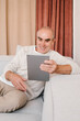 Happy retired man with tablet resting on sofa