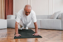 Positive Aged Man Doing Plank Exercise At Home