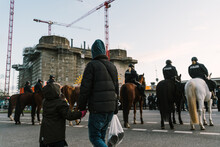 People Walking Behind A Formation Of Police Officers On Horses