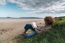 Black Woman Reading On The Beach