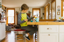 Young Child Alone Playing Drums On Glassware At Home