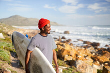 Surfer Exploring Rocky Shoreline For Surf