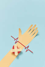 Papercraft Heart With Crossed Plaster Strips On A Hand.