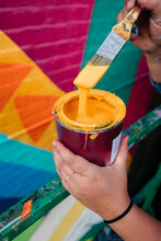 Artist Holding Paintbrush And Paint Can With Dripping Yellow Paint Next To A Geometric Colorful Wall Mural