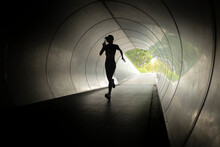 The Silhouette Of A Woman Running Through An Underpass In Singapore.