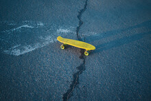 Yellow Skateboard And Crack In The Asphalt