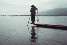 Man Fishing While Standing In Traditional Burmese Small Boat