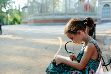 Kid Drawing On A Bench In A Park