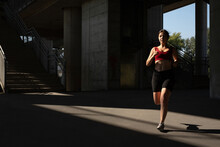 Woman Running On The Street, Under A Bridge