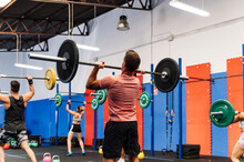 Unrecognizable Athletes Lifting Barbells Over Head