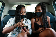 Two Young Women Checking Their Smart Phones Inside A Car